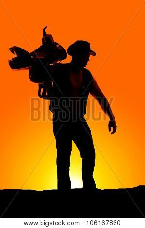 Silhouette Of A Cowboy Holding A Saddle On Shoulder Hand Out