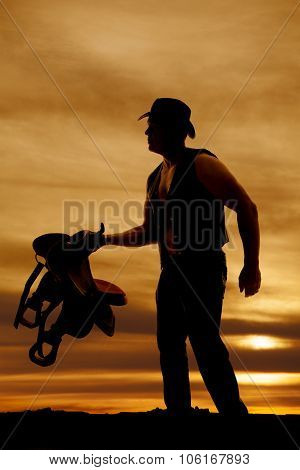 Silhouette Of A Cowboy Holding Out A Saddle In The Sunset