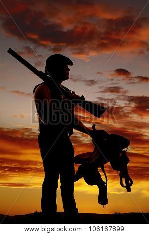 Silhouette Of A Cowboy In The Sunset Holding A Gun Over Shoulder And Saddle