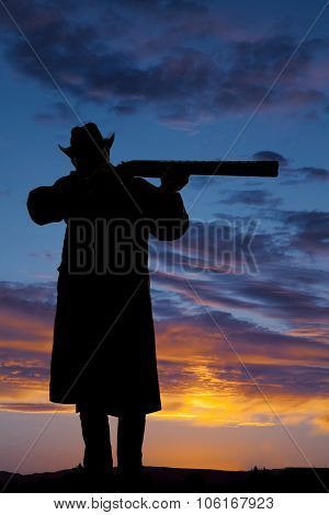 Silhouette Of A Cowboy Pointing A Rifle