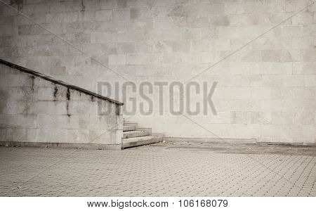 Weathered cinder block, brick wall texture with sidewalk and stair