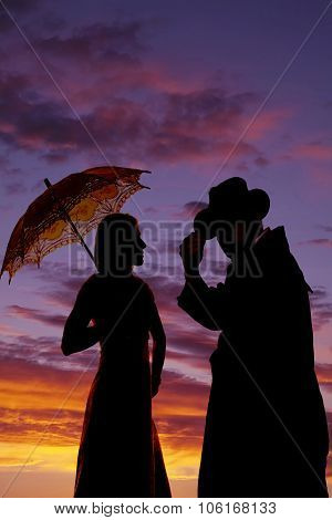 Silhouette Of Cowboy And Woman With Umbrella Close In Sunset