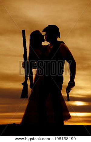 Silhouette Of Cowboy Couple Close With Guns