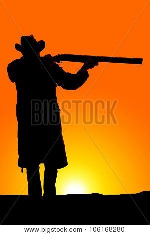 Silhouette Of Cowboy In Coat Aiming A Gun