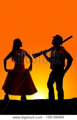 Silhouette Of Woman Hold Skirt And Cowboy With Gun In Sunrise