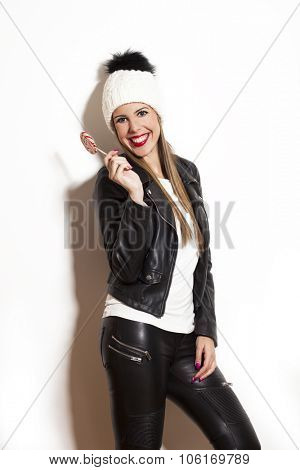 smiling beautiful long hair young woman with lollipop, wearing wool cap, black leather jacket and leggings, studio white