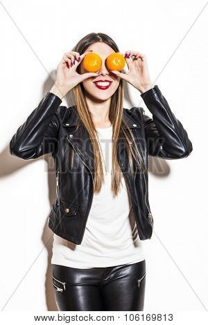 smiling young woman with tangerines on her eyes making fun, wearing black leather jacket and leggings, studio white