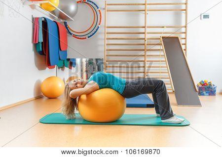 Young woman doing gymnastic exercises on a gym ball.