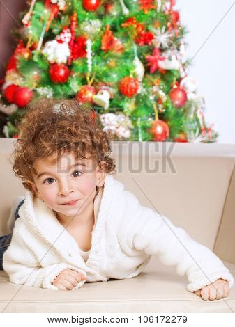 Portrait of cute adorable little boy lying down on the couch near beautiful decorated Christmas tree, spending winter holidays at home