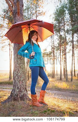Young Woman With Umbrella In Sunset Lights In Forest