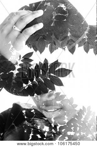 Double exposure portrait of a woman hiding her eyes with a hat combined with photograph of tree