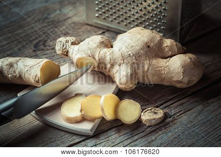 Ginger On Cutting Board And Grater On Kitchen Table. Selective Focus.