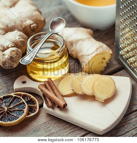Ginger On Cutting Board, Jar Of Honey, Dried Lemon Slice, Cinnamon And Grater On Kitchen Table.