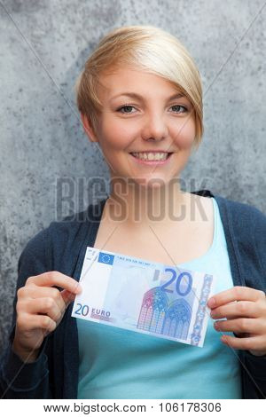 Attractive young woman holding twenty euro note