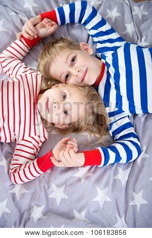 Two Cute Siblings Lying On Bed. Fokus Frome Above