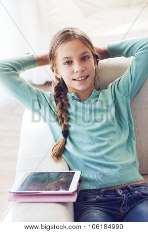 Preteen school girl of 8-9 years old playing on tablet pc at home