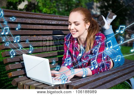 Happy Teenage Girl Listening Music With Laptop On Bench In Park