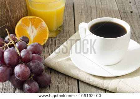 Cup of coffee with orange, juice, grapes, coco on a natural background. Table made of wood