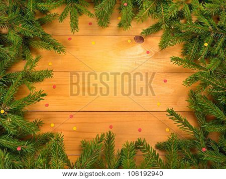 Christmas Tree Branches Frame On The Wooden Background With Confetti