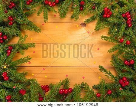 Christmas Tree And Red Berries Frame On The Wooden Background With Confetti