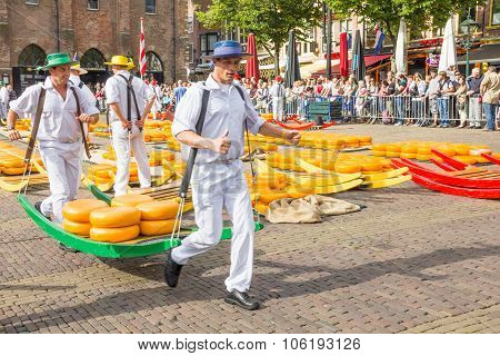 Carriers Walking With Many Cheeses In The Alkmaar market