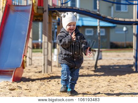Child Shakes Off His Hands From The Sand On Playground