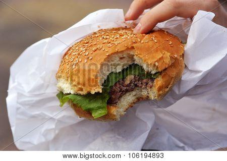 Hand holding a bitten hamburger