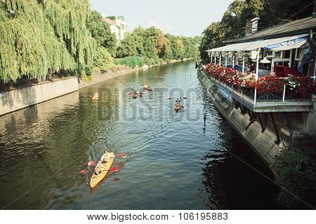 Some Sport Boats Kayaks Floating On River Under Green Trees