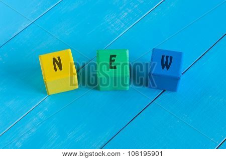 NEW - sign on color wooden cubes with light blue wood background.