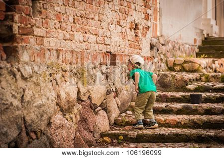 Little boy looking through a hole in wall