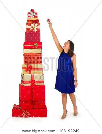Young woman putting one little gift on top of a huge stack of christmas presents