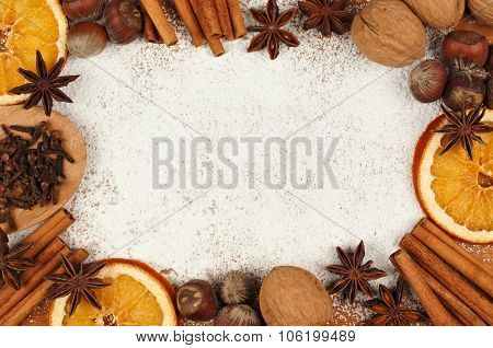 Holiday baking frame with nuts, spices and powdered sugar background
