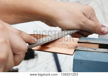Grinding the copper billet with a file