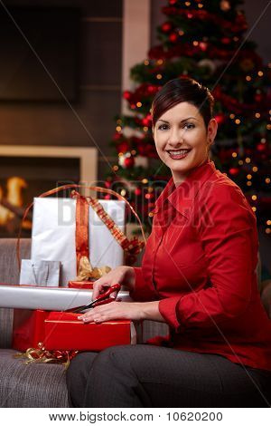 Young Woman Wrapping Gifts At Christmas