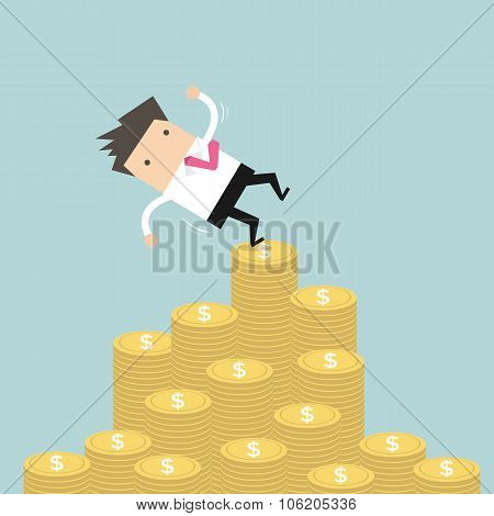 Businessman falling of money mountain