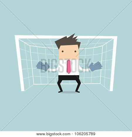 Businessman playing goalkeeper standing in front of goal