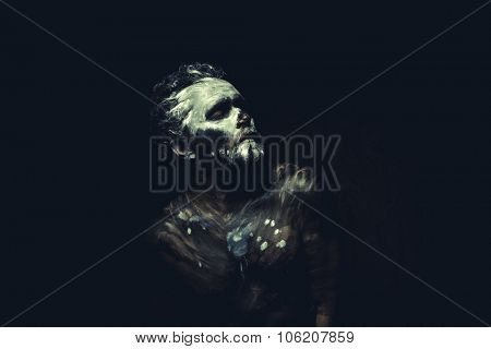 Warrior, wild man with white painted face and full body black paint