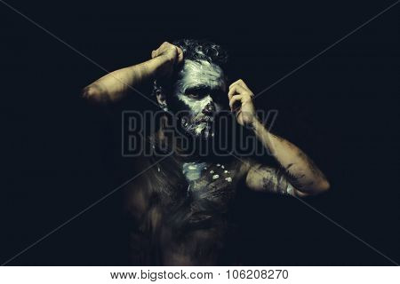 Fight, wild man with white painted face and full body black paint