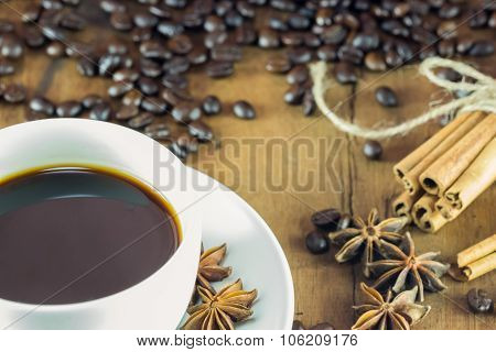 Coffee On The Cup With Coffee Beans And Cinnamon Sticks On Wood Background ,  Warm Toning, Selective