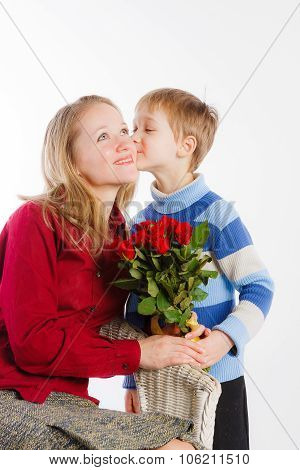 Little child giving bouquet to his mom and kissing her