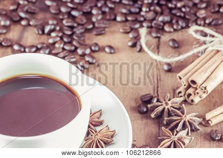 Coffee On The Cup With Coffee Beans And Cinnamon Sticks On Wood Background ,  Vintage Toning, Select