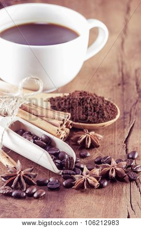 Coffee On The Cup With Coffee Beans And Cinnamon Sticks On Wood Background, Vintage Toning, Selectiv