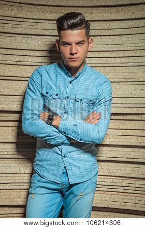sexy boy in denim posing in studio with hands crossed while looking at the camera