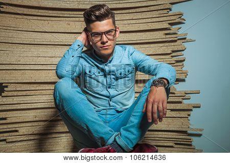 portrait of smart man wearing glasses while sitting legs crossed in wooden studio