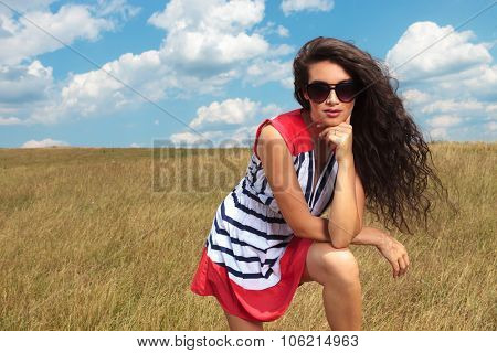 Gorgeous young woman leaning hear chin on her hand while looking at the camera.