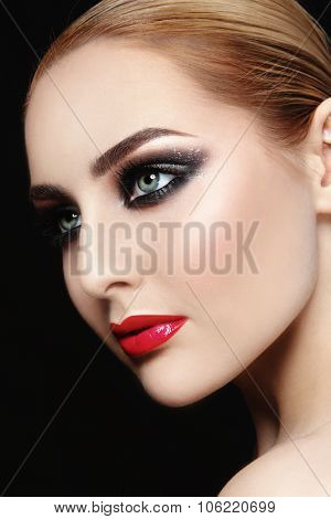 Close-up portrait of young beautiful woman with red lips and smoky eyes