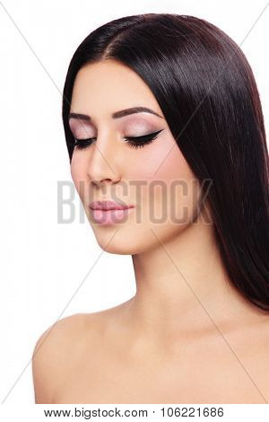 Young beautiful tanned brunette with winged eyes over white background, copy space