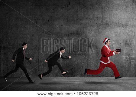 Business People Chasing Santa Claus