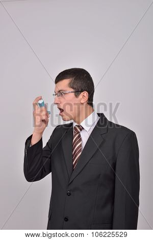 Young Caucasian Man In Suit Using An Asthma Inhaler To Handle Problems With Breathing