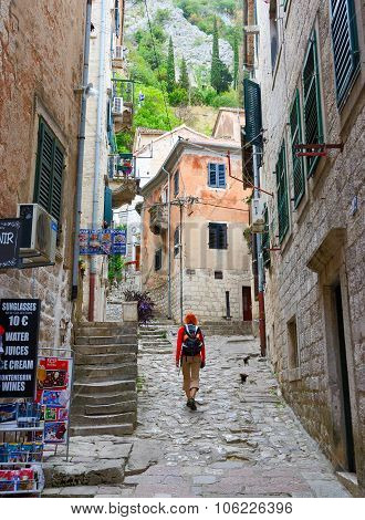 Girl Tourist Goes On Narrow Street Of Old Town, Kotor, Montenegro